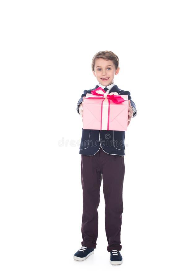 entzückender stilvoller kleiner Junge, der Geschenkbox hält und an der Kamera lächelt lizenzfreie stockfotos