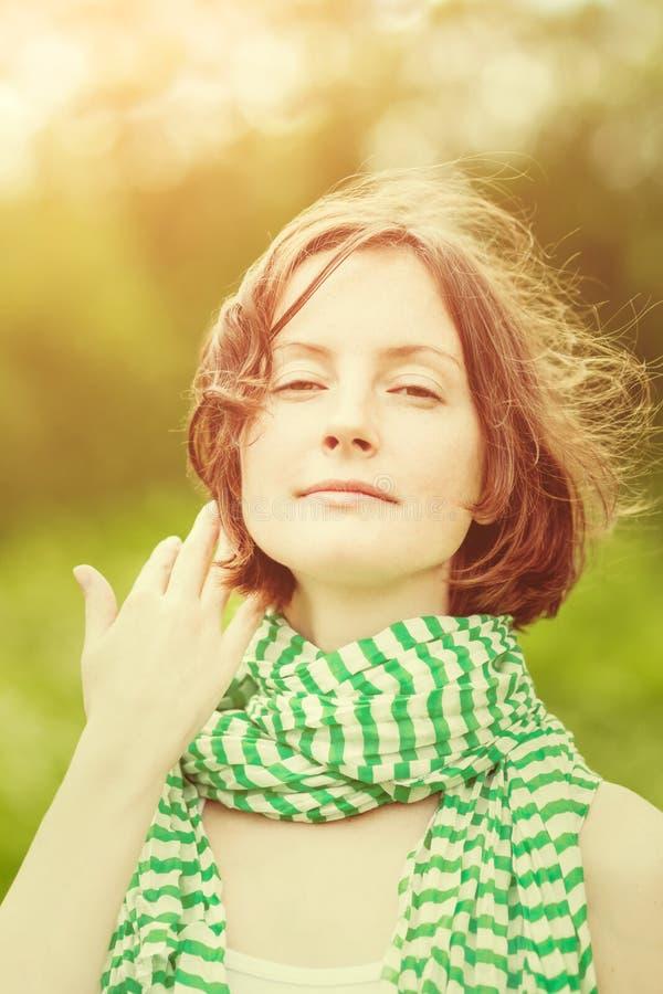 Entzückender tragender gestreifter Schal der jungen Frau mit Wind in ihrem Haar lizenzfreie stockfotografie