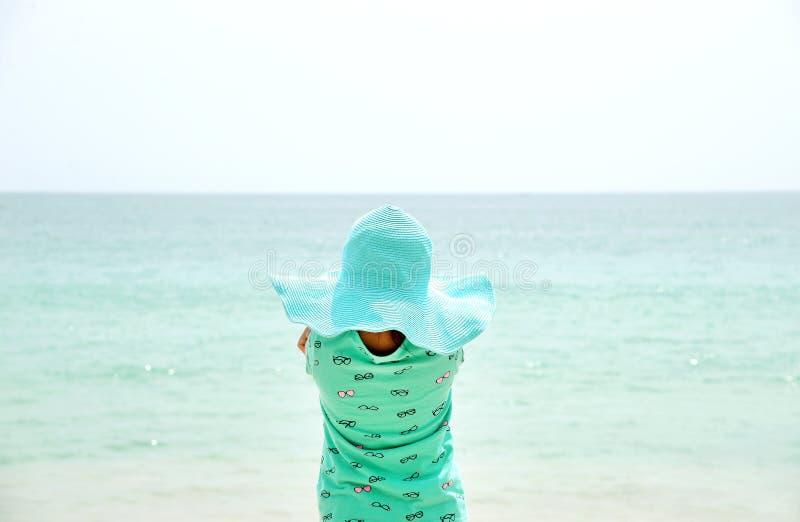 Entzückender tragender Hut des kleinen Mädchens, der am Strand während der Sommerferien steht lizenzfreie stockfotografie