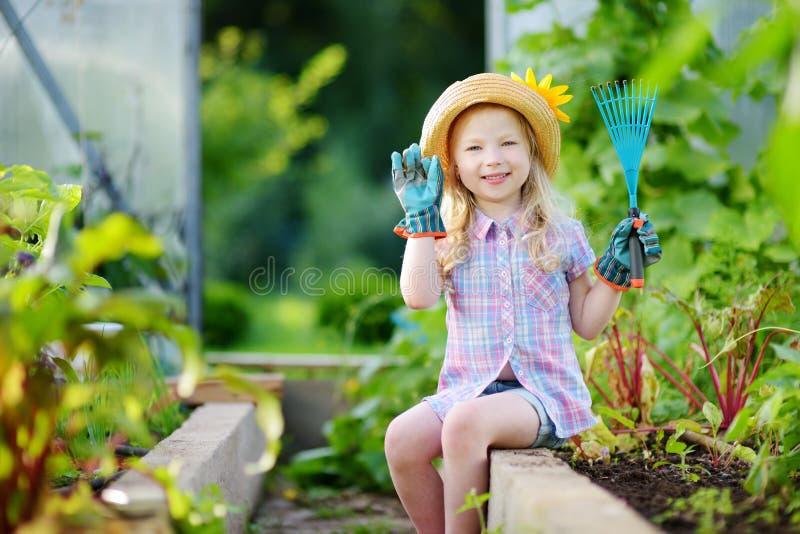 Entzückender tragender Strohhut des kleinen Mädchens und Gartenhandschuhe der Kinder, die mit ihren Spielzeuggartenwerkzeugen in  stockbild