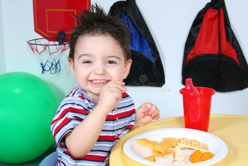 Entzückender Vorschüler, der Imbisse isst stockfoto