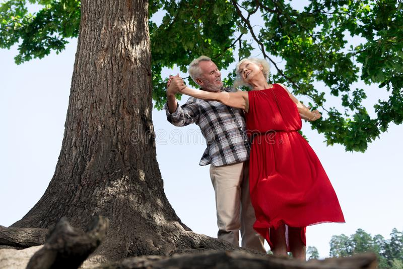 Entzückendes älteres Paartanzen durch den Baum und das Lächeln stockfoto