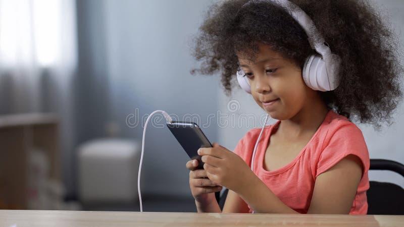 Entzückendes afrikanisches Mädchenkindertragende Kopfhörer, hörend Musik auf Mobiltelefon lizenzfreies stockfoto