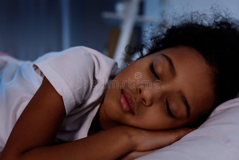 entzückendes Afroamerikanerkind, das im Bett schläft stockfotografie
