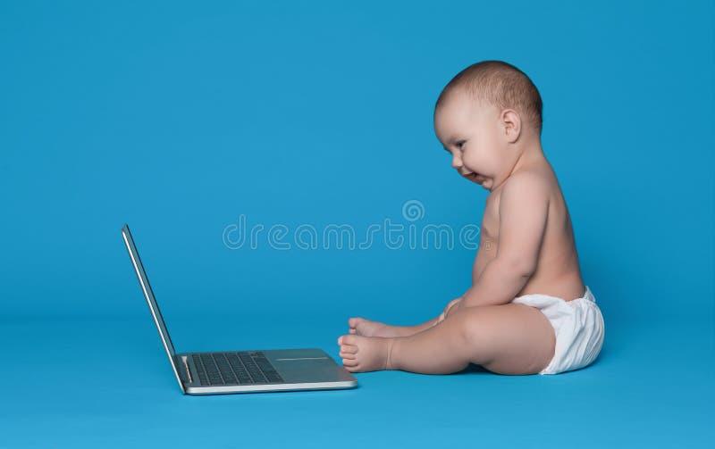Entzückendes Baby, das auf Boden sitzt und Laptopschirm betrachtet stockfoto