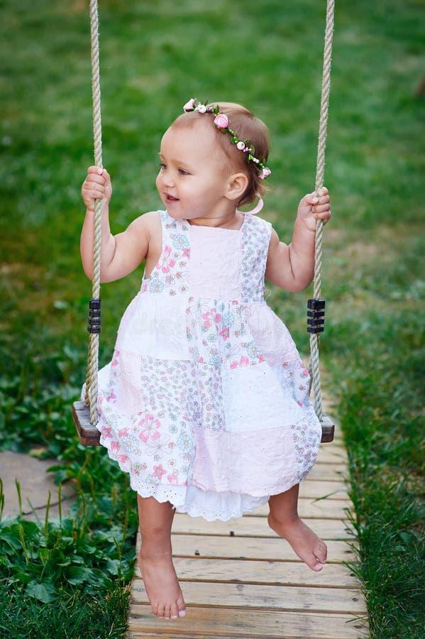 Entzückendes Baby, das eine Schwingenfahrt auf einen Spielplatz in einem Park genießt stockfotografie