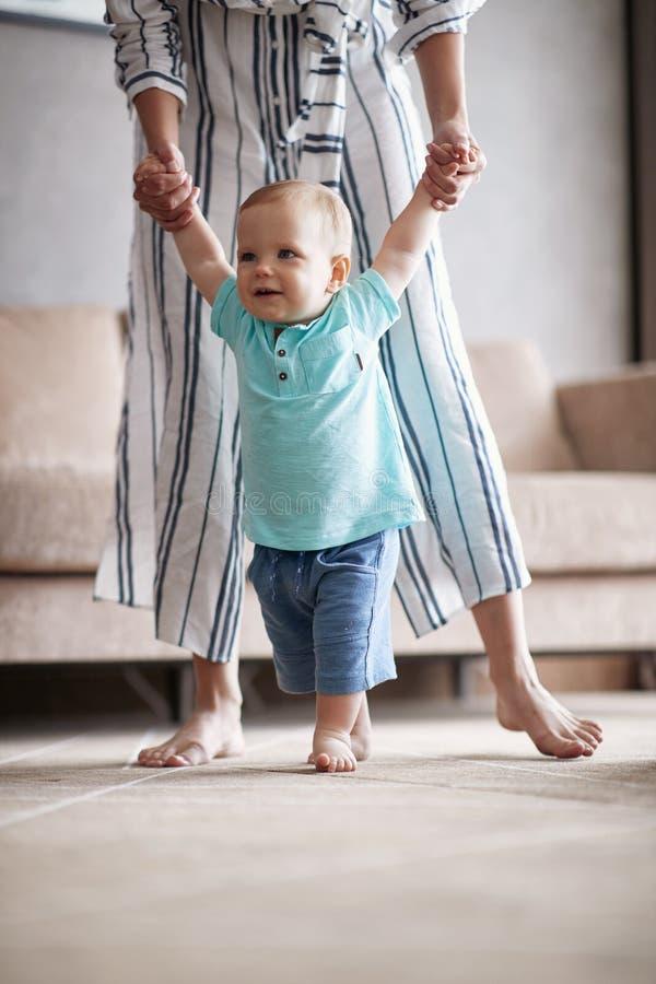 Entzückendes Baby, das erste Schritte mit Mutter macht stockfoto