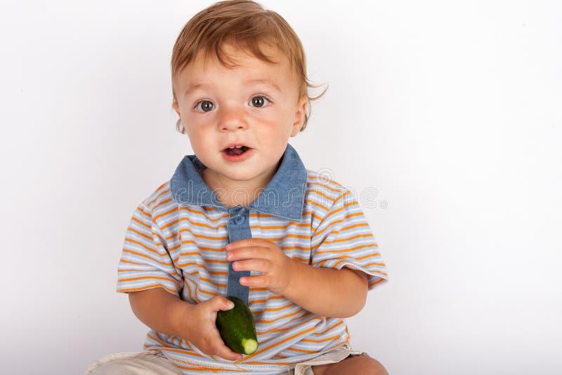 Entzückendes Baby, das Gurke isst lizenzfreies stockbild