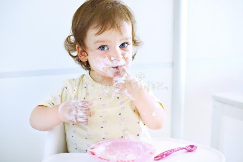 Entzückendes Baby, das mit Lebensmittel spielt Kind, das Joghurt isst Schmutziges Gesicht des glücklichen Kindes Porträt eines Ba lizenzfreie stockbilder