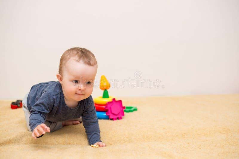 Entzückendes Baby, das mit pädagogischen Spielwaren spielt Hintergrund mit Kopienraum Glückliches gesundes Kind, das Spaß zu Haus lizenzfreie stockbilder