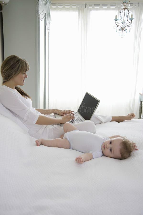 Entzückendes Baby, das neben der Mutter verwendet Laptop liegt stockfotos