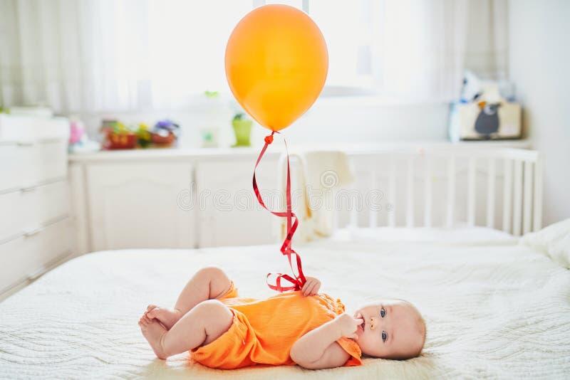 Entzückendes Baby in der orange Spielanzugklage mit buntem Ballon lizenzfreie stockbilder