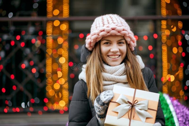 Entzückendes blondes Mädchen, das gestrickte rosa Kappen- und Schalholding trägt stockbild