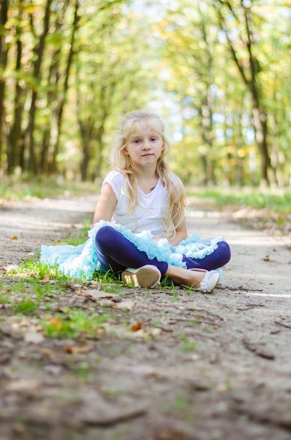 Entzückendes blondes Mädchen im blauen Ballettröckchenrock, der im ländlichen Weg im Wald sitzt lizenzfreies stockfoto