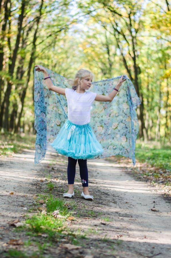 Entzückendes blondes Mädchen im blauen Ballettröckchenrock, der mit blauem scard aufwirft lizenzfreies stockfoto
