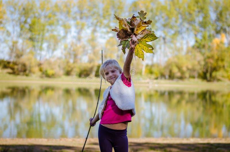 Entzückendes blondes Mädchen mit orange Blättern lizenzfreie stockfotografie