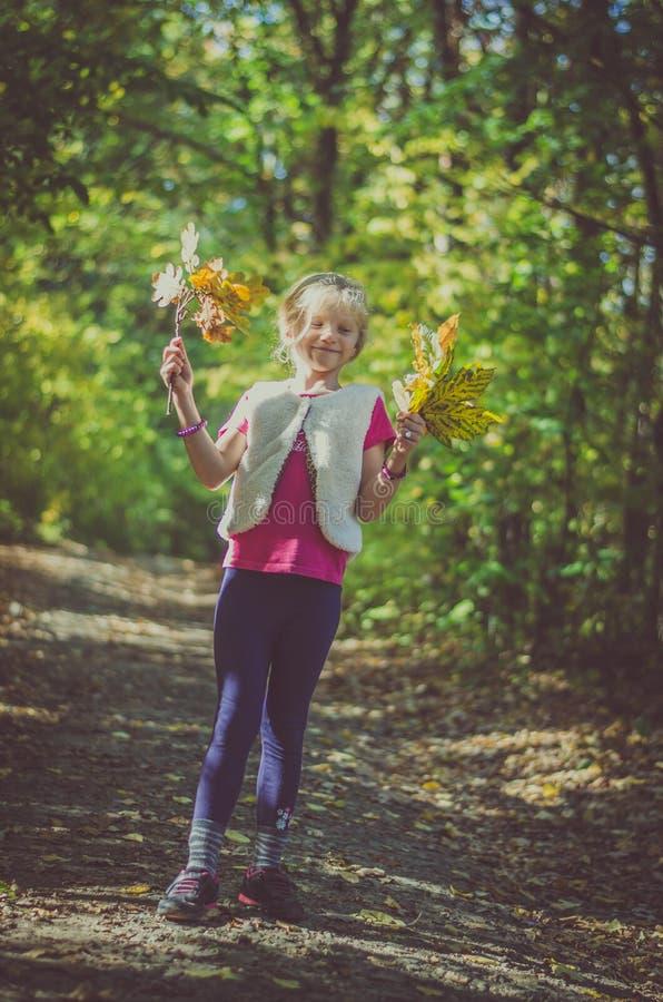 Entzückendes blondes Mädchen mit orange Blättern stockbild