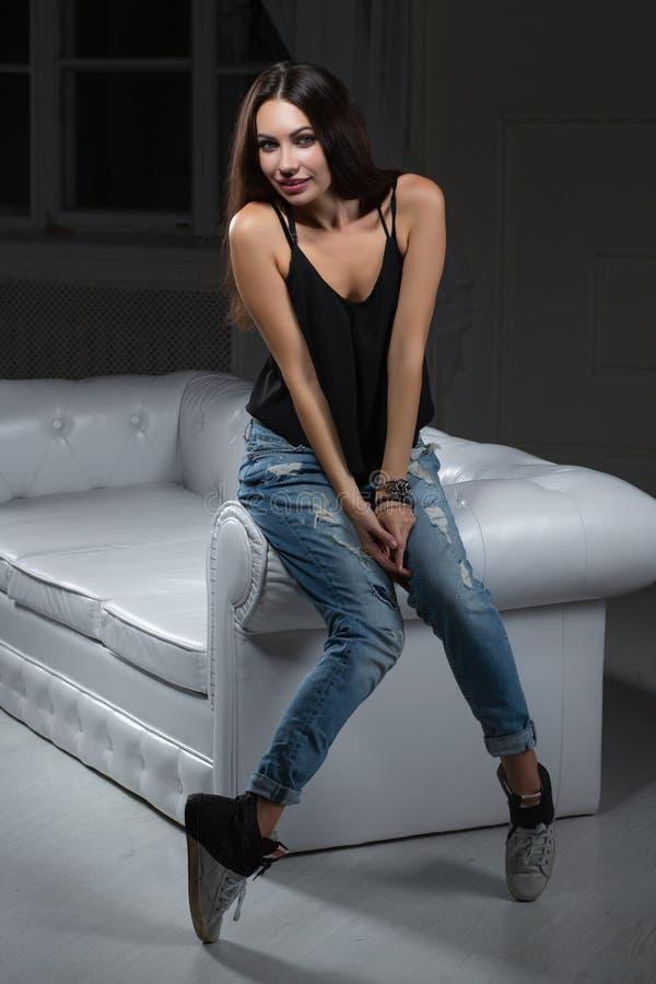 Entzückendes brunette Aufstellungsc$sitzen auf einem Sofa lizenzfreie stockfotos