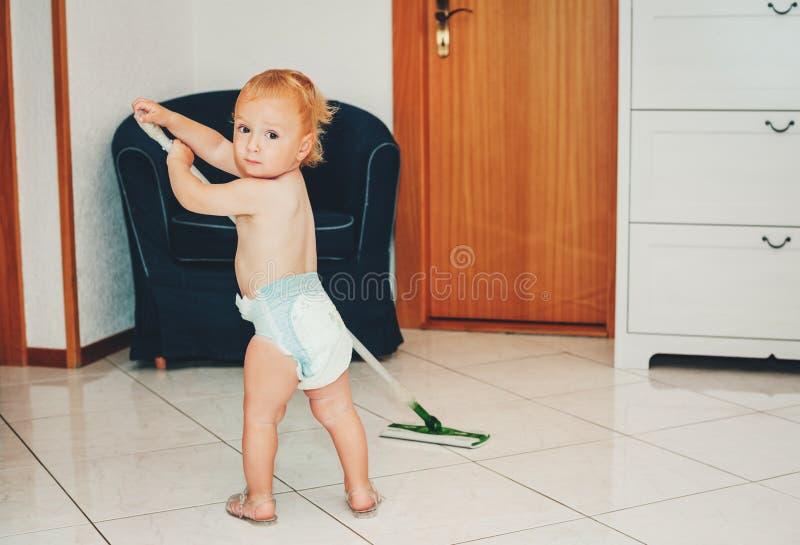 Entzückendes einjähriges Baby, das bei der Reinigung hilft lizenzfreies stockfoto