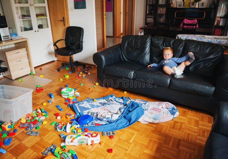 Entzückendes einjähriges Baby mit dem lustigen Gesichtsausdruck, der in einem sehr unordentlichen Wohnzimmer spielt lizenzfreies stockbild