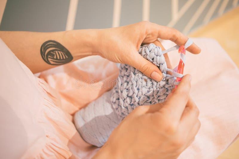 Entzückendes entspanntes strickendes Häkelarbeithobby Frau im rosafarbenen Kleid Freizeitschaffung von Kleidung lizenzfreie stockfotos