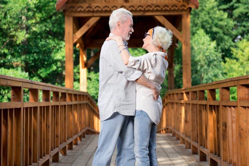 Entzückendes gealtertes Paartanzen beim Sein auf der Brücke lizenzfreies stockfoto