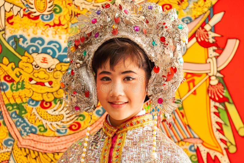 Entzückendes Gesicht einer chinesischen Opernschauspielerin im schönen traditionellen Kostüm, lächelnd an der Kamera, bunt vom tr lizenzfreie stockbilder