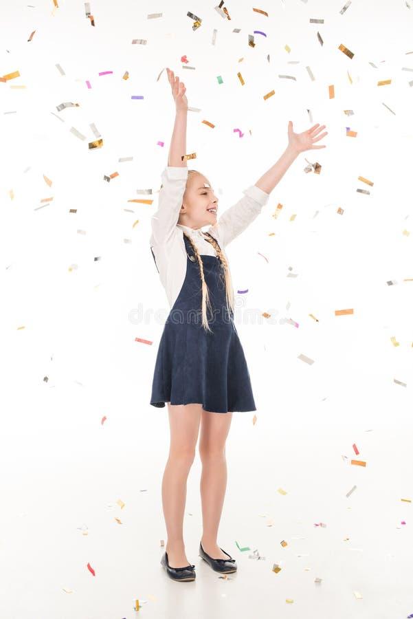 entzückendes glückliches kleines Mädchen, das mit Konfettis spielt stockbild