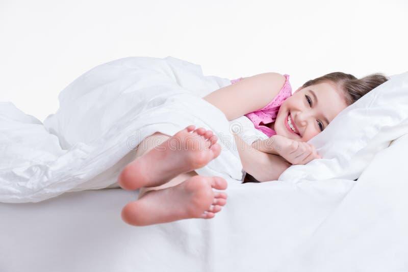 Entzückendes glückliches kleines Mädchen im rosa Nachthemd wach. stockbilder