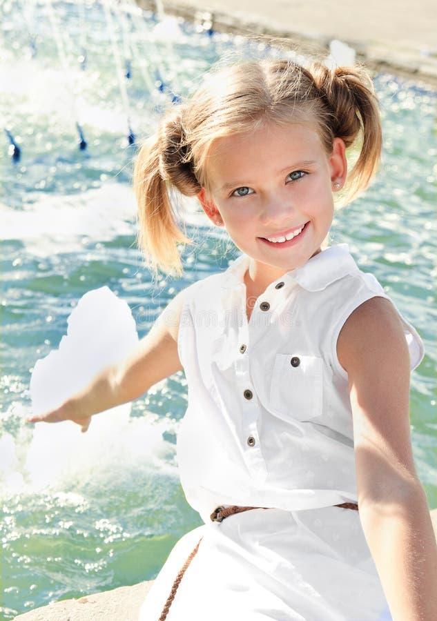Entzückendes glückliches lächelndes Kind des kleinen Mädchens, das nahe dem founta sitzt lizenzfreie stockbilder