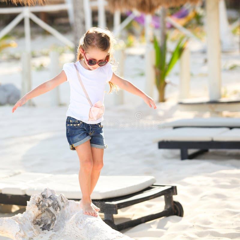 Entzückendes glückliches lächelndes kleines Mädchen auf Strand stockfotos