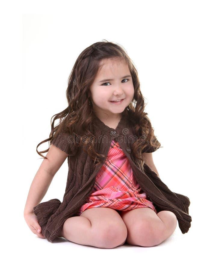 Entzückendes junges Kind, das auf ihrem Kn lächelt und sitzt stockfotografie