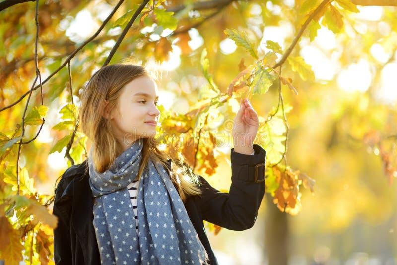 Entzückendes junges Mädchen, das Spaß am schönen Herbsttag hat Gl?ckliches Kind, das im Herbstpark spielt Kind, das gelben Herbst stockfoto