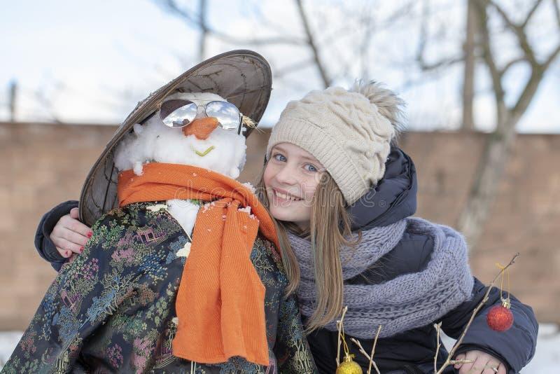 Entzückendes junges Mädchen mit einem Schneemann im schönen Winterpark Winterbetriebe für Kinder stockbild