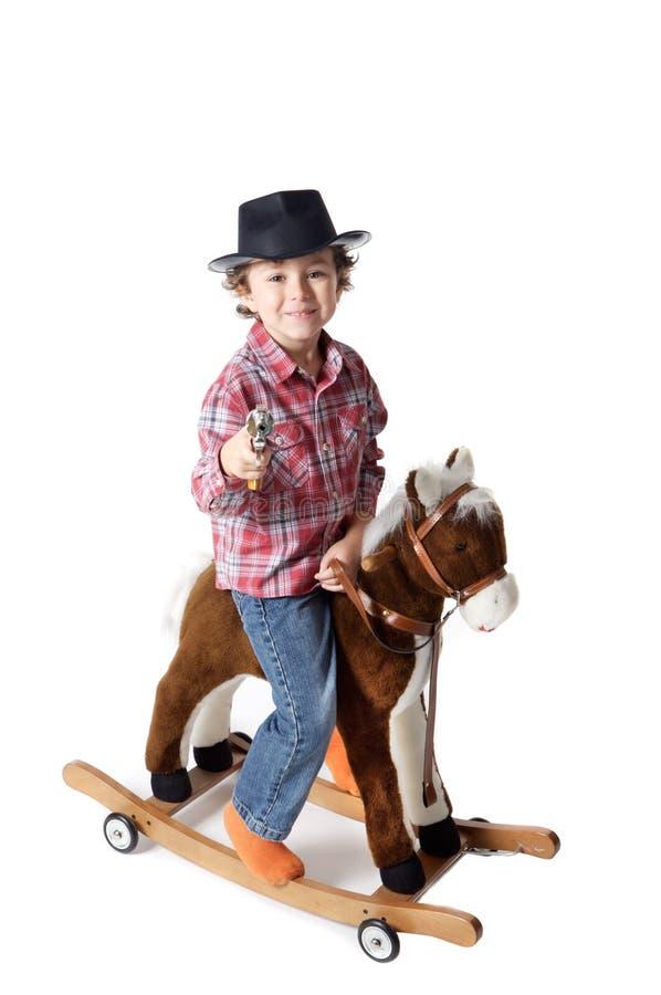 Entzückendes Kind, das ein Spielzeugpferd reitet lizenzfreie stockbilder