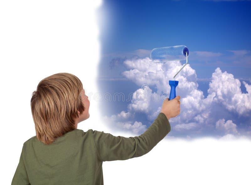 Entzückendes Kind, das einen schönen Himmel mit einer Rolle malt stockfotografie