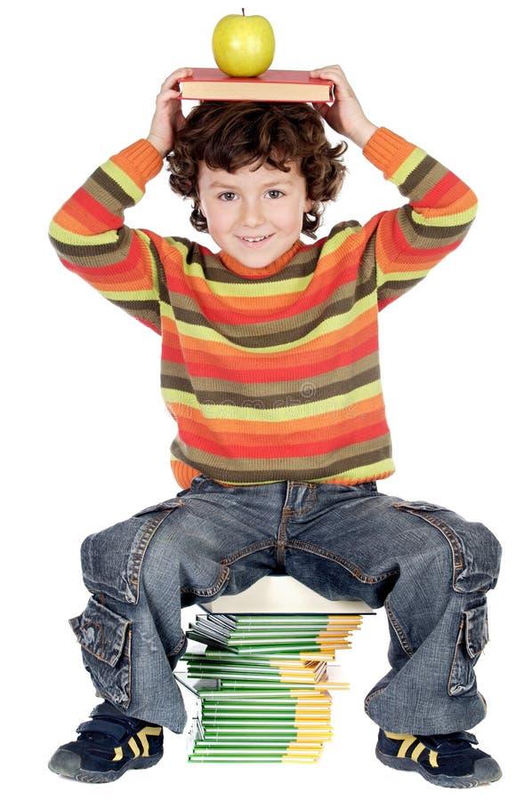Entzückendes Kind, das mit Büchern und Apfel im Kopf studiert stockbilder