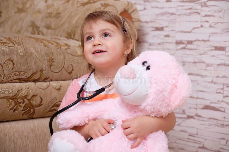 Entzückendes Kind, das zu Hause Doktor oder Krankenschwester mit Plüschspielwaren spielt lizenzfreies stockfoto