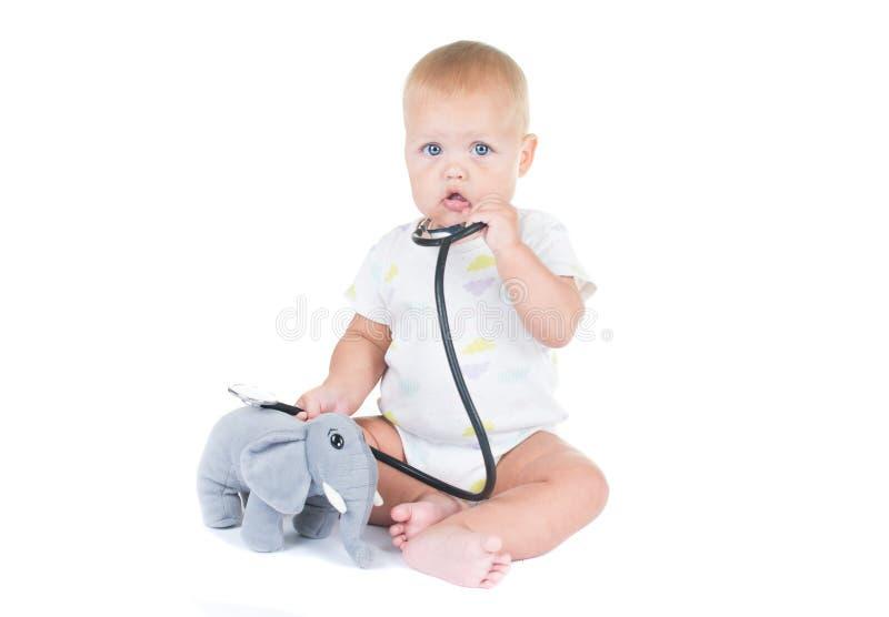 Entzückendes Kind gekleidet als Doktor, der mit dem Spielzeug lokalisiert auf weißem Hintergrund spielt stockfotografie
