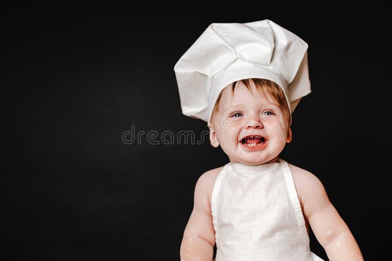 Entzückendes Kind im Hut des Kochs und des Schutzblechs stockfoto