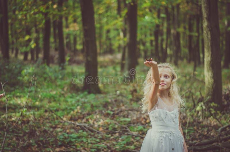 Entzückendes Kind im langen weißen Heiratskleid mit Schmetterling in den Händen lizenzfreies stockfoto