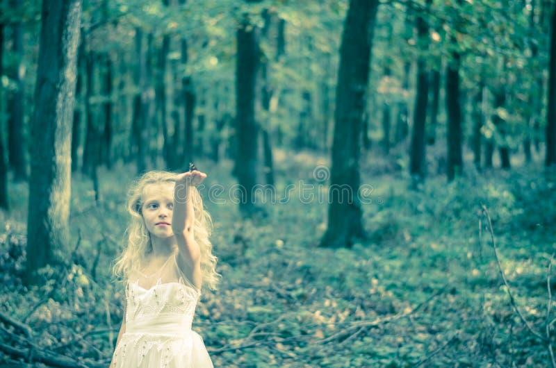 Entzückendes Kind im langen weißen Heiratskleid mit Schmetterling in den Händen lizenzfreie stockfotografie