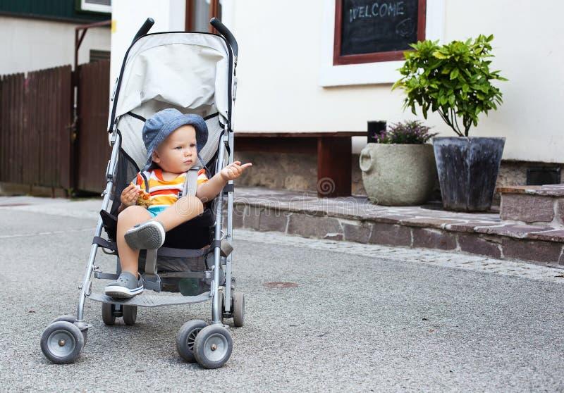 Entzückendes Kinderkleinkind in einem Spaziergänger auf der Straße lizenzfreies stockbild