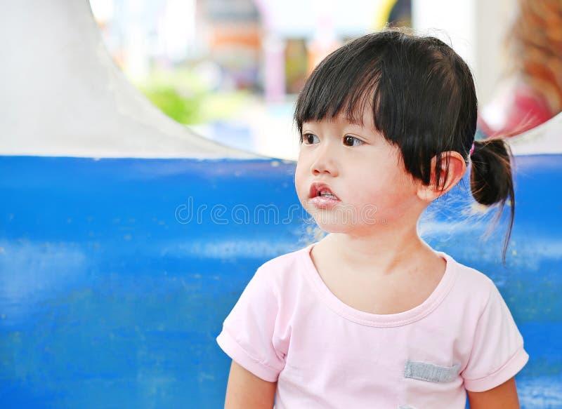 Entzückendes Kindermädchen, das auf einem Wagen in einem Karussell lächelt stockbild