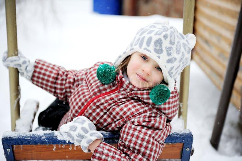 Entzückendes Kindmädchen genießt ständiges Schwanken im Winter lizenzfreie stockfotos