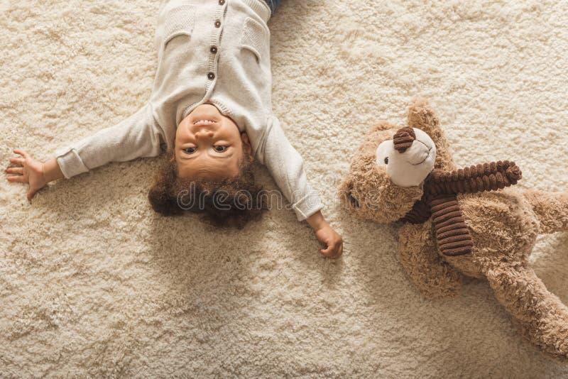 Entzückendes kleines Afroamerikanermädchen, das zu Hause auf Teppich liegt stockfotografie