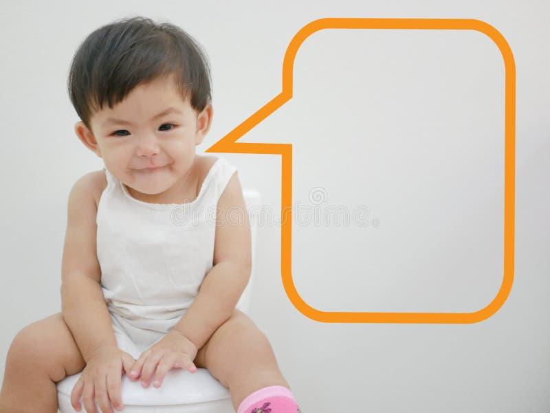 Entzückendes kleines asiatisches Baby genießt, auf einer Babygrößentoilette mit einer Spracheblase zu sitzen, die bereit ist gefü lizenzfreie stockfotografie