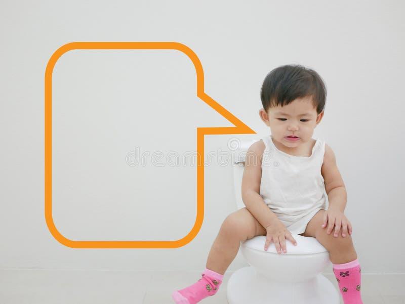 Entzückendes kleines asiatisches Baby genießt, auf einer Babygrößentoilette mit einer Spracheblase zu sitzen, die bereit ist gefü lizenzfreie stockbilder
