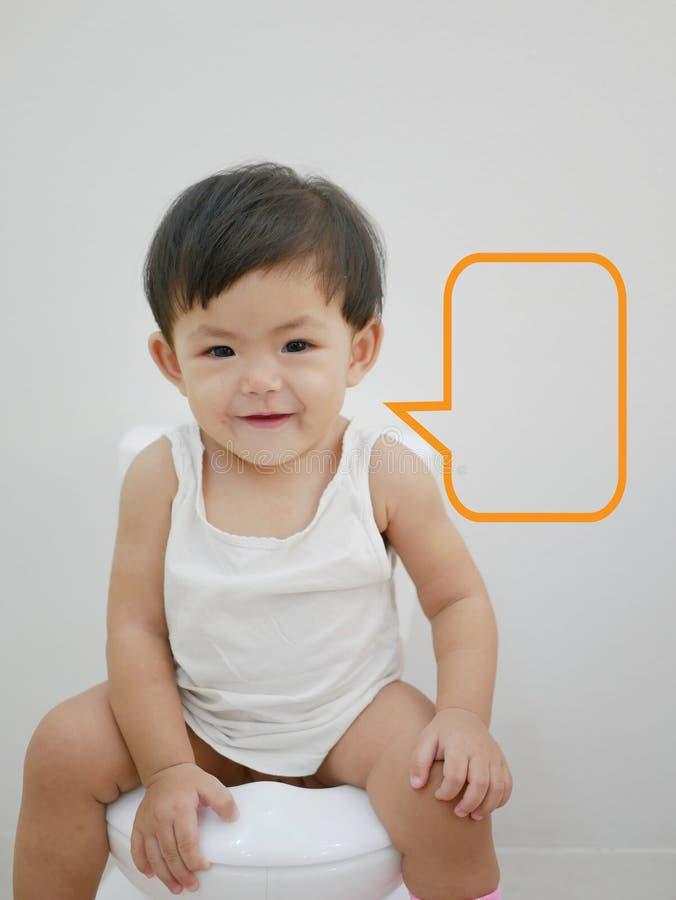 Entzückendes kleines asiatisches Baby genießt, auf einer Babygrößentoilette mit einer Spracheblase zu sitzen, die bereit ist gefü stockbilder