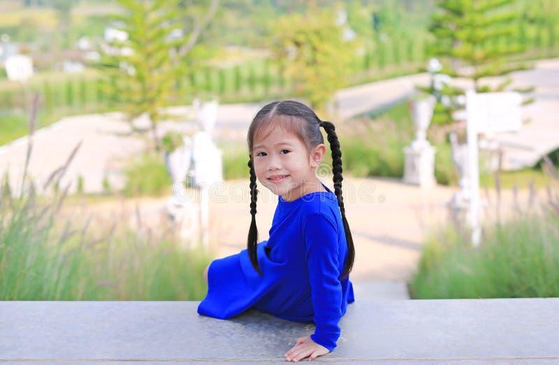 Entzückendes kleines asiatisches Kindermädchen, das auf Treppe im Garten mit dem Schauen der Kamera sitzt lizenzfreies stockbild